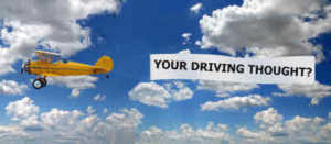 """biplane towing a banner asking, """"Your Driving Thought?"""""""